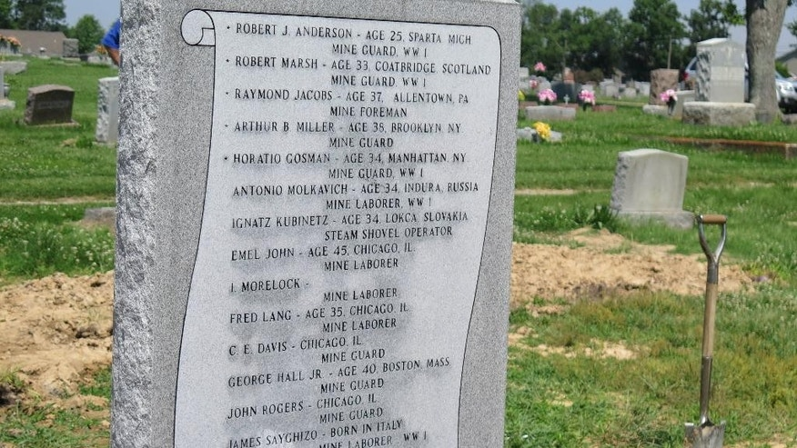 In this June 10, 2015 photo, a new burial marker commemorating 17 victims of the 1922 Herrin Massacre is seen at the municipal cemetery in the southern Illinois town  of Herrin, Ill. A team of local historians and university scientists spent several years working to identify the location of the previously unmarked graves. The clash between striking coal miners and a group of replacement workers and guards was one of the nation's deadliest labor disputes. (AP Photo/Alan Scher Zagier)