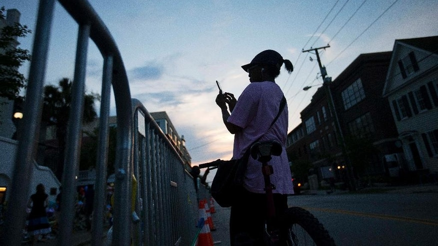 A passing cyclist stops to take a photo at a sidewalk memorial in memory of the shooting victims in front of Emanuel AME Church at sunrise Saturday, June 20, 2015, in Charleston, S.C. (AP Photo/David Goldman)