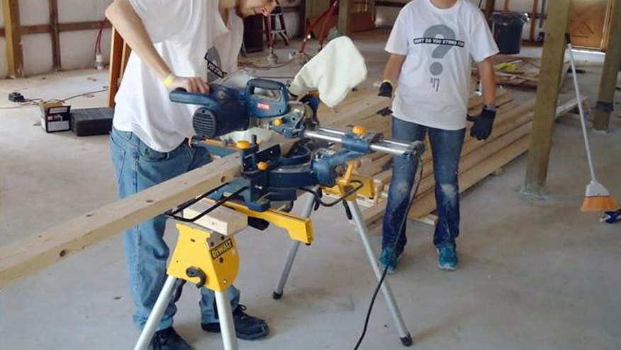 In this July 23, 2013 photo released by Ben's Lighthouse, Trystan Wagner uses a table saw to make a cut during the group's building project after tornadoes caused destruction in Moore, Okla. The annual service trip is run by Ben's Lighthouse, a nonprofit founded to help children from Newtown, Conn., recover from the December 2012 massacre at Sandy Hook Elementary School. The organization is named after 6-year-old victim Ben Wheeler. The third annual trip will be in July 2015 to help rebuild homes devastated in the previous year's flooding. (Ben's Lighthouse/Jen Marlin via AP)