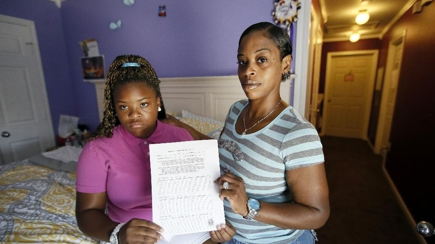 Natod'Ja Washington, left, 16, poses for a photo with her mother Natasha Holloway in their home as they hold a student sign in sheet for truancy court Friday, June 19, 2015, in Dallas. The form must be signed by all of her teachers confirming Washington's attendance in school. (AP Photo/Tony Gutierrez)
