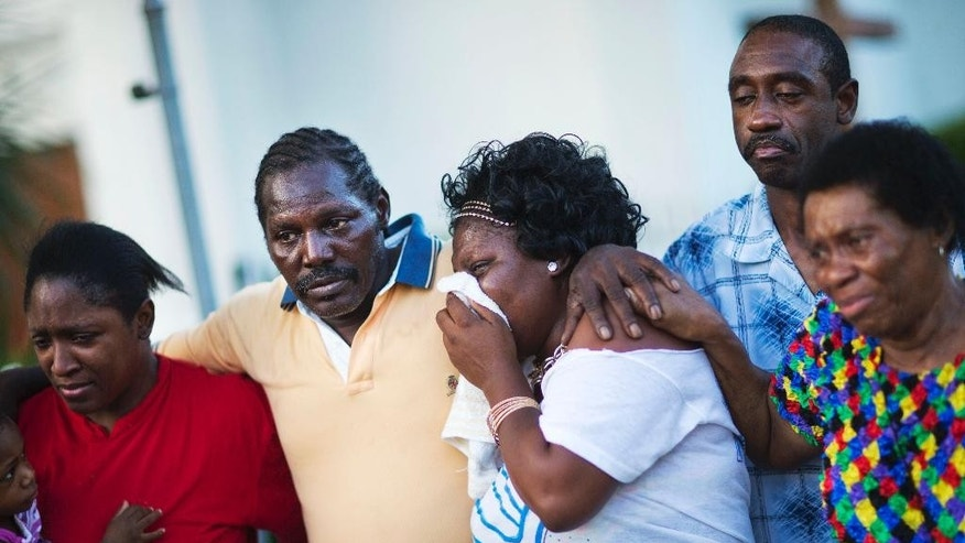 Gary and Aurelia Washington, center left and right, the son and granddaughter of Ethel Lance who died in Wednesday's shooting, leave a sidewalk memorial in front of Emanuel AME Church comforted by fellow family members Thursday, June 18, 2015, in Charleston, S.C. The current brick Gothic revival edifice, completed in 1891 to replace an earlier building heavily damaged in an earthquake, was a mandatory stop for the likes of Booker T. Washington and the Rev. Martin Luther King Jr. Still, Emanuel was not just a church for the black community. (AP Photo/David Goldman)