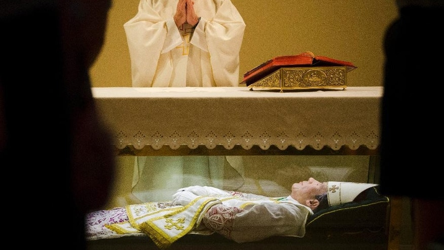 The Rev. John McLoughlin, Pastor of Our Mother of Perpetual Help in Ephrata, Pa., prays over the remains of  Saint John Neumann Tuesday, May 5, 2015, at the national shrines of St. John Neumann in Philadelphia. At the Neumann shrine, tucked in a commercial area in North Philadelphia, visitors can view remains of the saint, who was the fourth bishop of Philadelphia and is credited with expanding the Catholic education system in the U.S. (AP Photo/Matt Rourke)