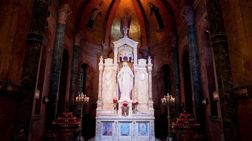 A statue of Our Lady of the Miraculous Medal stands at an altar, Thursday, June 18, 2015, in Philadelphia. The Miraculous Medal shrine, in the residential Germantown neighborhood, features striking stained glass windows and the sculpture dedicated to Mary.   (AP Photo/Matt Rourke)