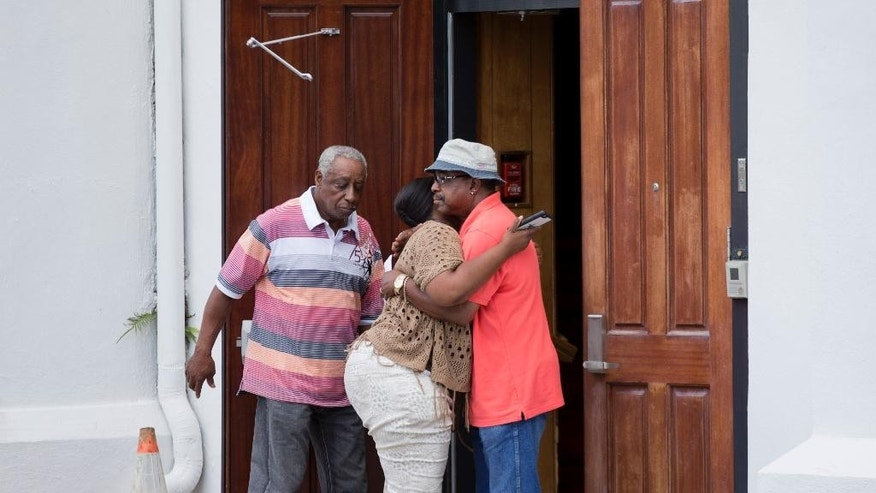 Cassie Watson, right, embraces a fellow church member as the doors to Emanuel AME Church open after a cleaning crew finished working  Saturday, June 20, 2015, in Charleston, S.C. Congregation members say the historic black church where nine people were killed is going to re-open for Sunday morning service. (AP Photo/David Goldman)