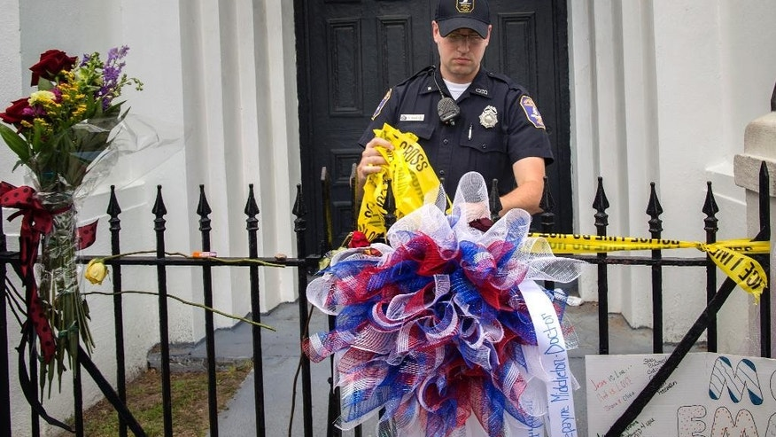 A Charleston police officer removes the crime scene tape from the wrought iron fence in front of the Emanuel AME Church, Saturday, June 20, 2015, in Charleston, S.C.  A constant stream of people have visited the site where nine people where killed by a gunman while attending bible study. (AP Photo/Stephen B. Morton)