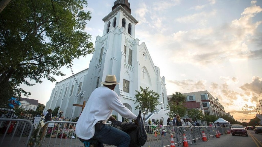 A bicyclist rides in front of the Emanuel AME Church, Sunday, June 21, 2015, before the first worship service since nine people were fatally shot at the church during a Bible study group, in Charleston, S.C. (AP Photo/Stephen B. Morton)