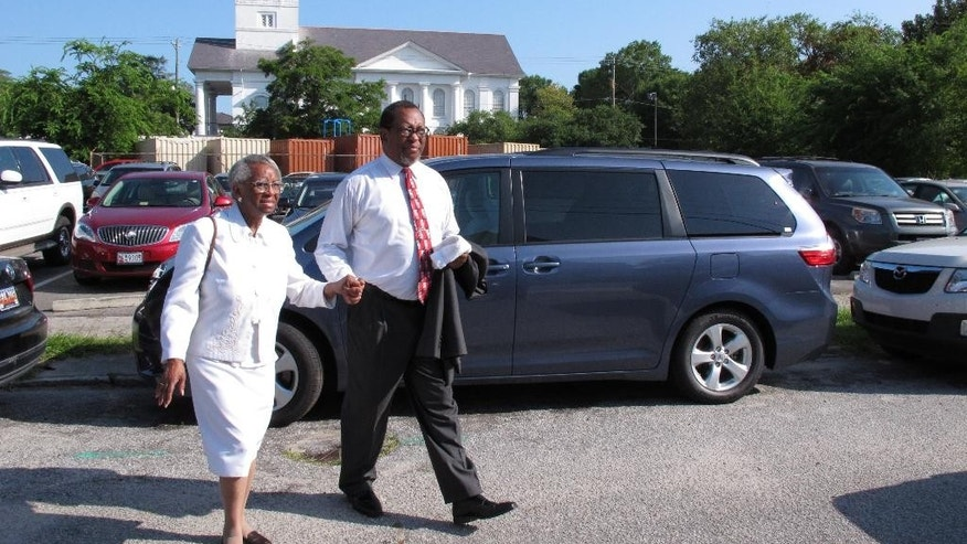 LeVanza Breeland escorts his mother, Felicia, to services at Emanuel African Methodist Episcopal Church in Charleston, S.C., on Sunday, June 21, 2015. The 81-year-old woman, whose family have been members at Emanuel for four generations, said the coordinated ringing of church bells in honor of nine people slain in her congregation's Bible study was a beautiful show of unity. (AP Photo/Allen G. Breed)
