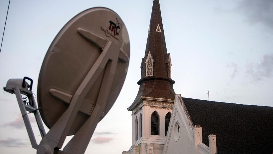 A media satellite dish points to the sky in front of the Emanuel AME Church Sunday, June 21, 2015, before the first worship service since nine people were fatally shot at the church during a Bible study group, in Charleston, S.C. (AP Photo/Stephen B. Morton)