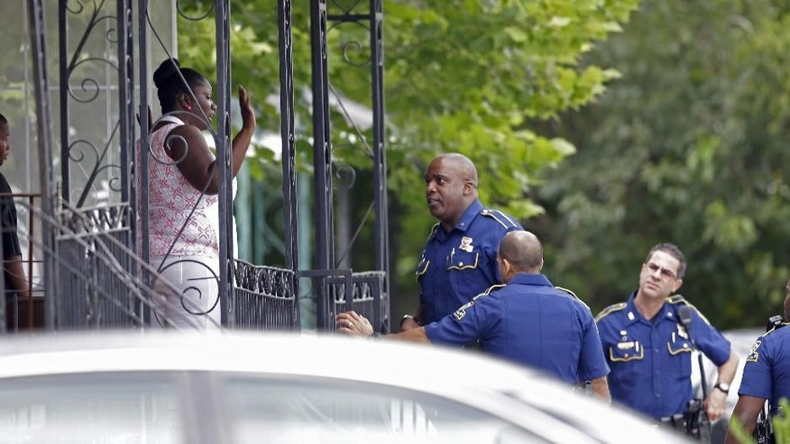 Louisiana State Police talk to people on a porch as they search for an escaped prisoner who shot and killed a New Orleans police officer in his vehicle while he was  transporting the prisoner in New Orleans, Saturday, June 20, 2015. The New Orleans Police Department said Officer Daryle Holloway was shot while transporting Travis Boys, who managed to get his handcuffed hands from behind his back to the front, grab a firearm and shoot the officer. A manhunt was underway for the 33-year-old Boys, according to Police Chief Michael Harrison. (AP Photo/Gerald Herbert)
