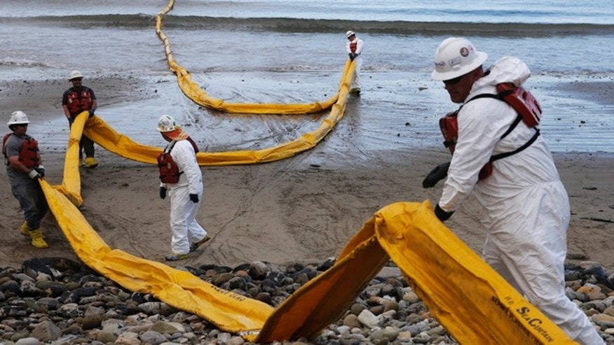 In this May 21, 2015 file photo, workers prepare an oil containment boom at Refugio State Beach, north of Goleta, Calif. Cleanup work continues one month after the May 19 oil spill north of Santa Barbara, Calif.