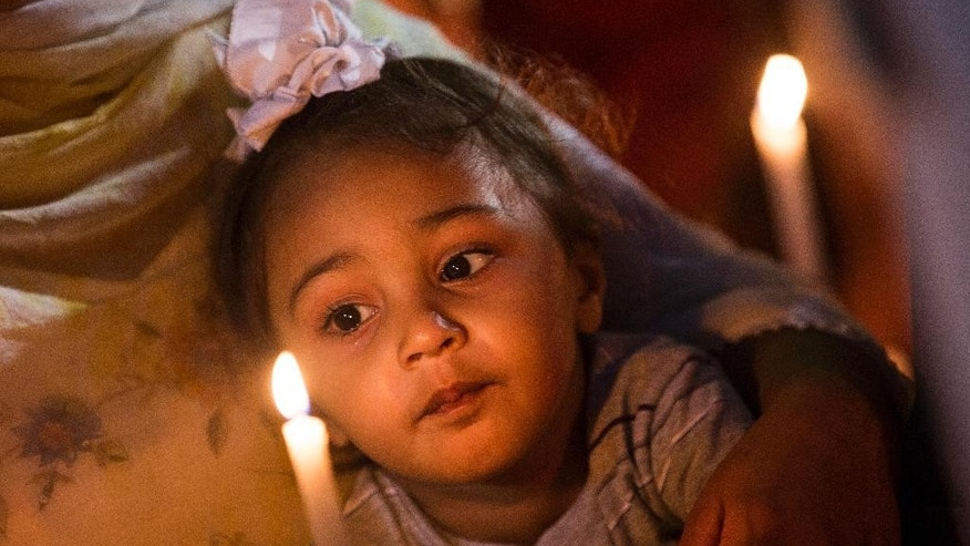 FILE - In this Tuesday, Aug. 7, 2012 file photo, a child looks at a candle during a vigil at the Oak Creek Civic Center in Oak Creek, Wis. for the victims of a mass shooting at the Sikh Temple of Wisconsin on Sunday. (AP Photo/Tom Lynn)