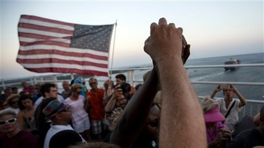 June 21: People raise their hands as a show of unity as thousands of marchers meet in the middle of Charleston's main bridge after nine black church parishioners were gunned down during a Bible study.