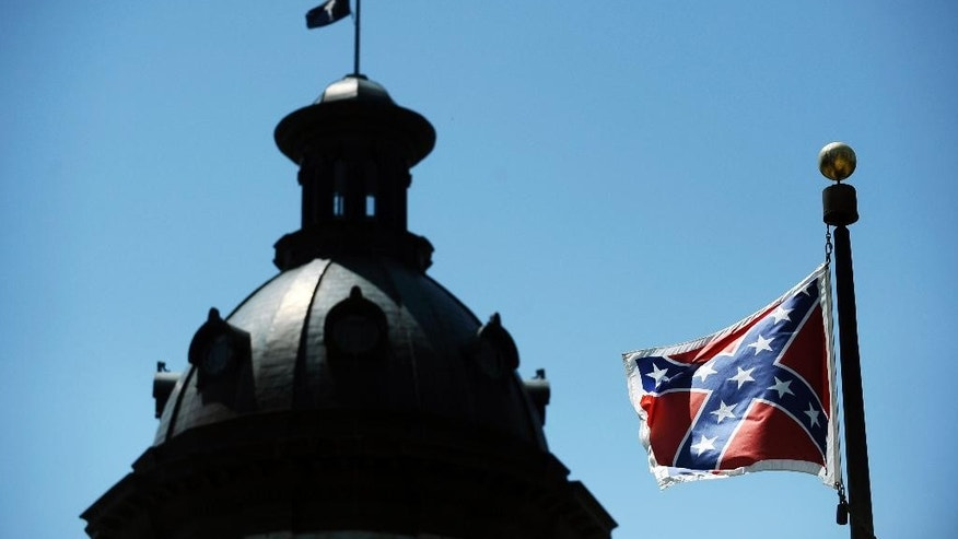 In this June 19, 2015, photo, a Confederate flag flies near the South Carolina Statehouse in Columbia, S.C.  Whether South Carolina should continue to fly the Confederate flag on its statehouse grounds is the latest in a series of issues to arise this summer challenging the GOP's effort to build the young and diverse coalition of voters it likely needs to win the White House.  (AP Photo/Rainier Ehrhardt)