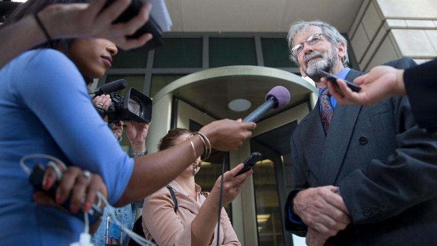 Douglas Hughes, right, the gyrocopter pilot who landed on the West Front of the U.S. Capitol, talks with members of the media outside of Federal Court after a status hearing Monday June 22, 2015, in Washington. Hughes said he's rejected a plea offer in the case that would have involved several years in prison.  (AP Photo/Jacquelyn Martin)