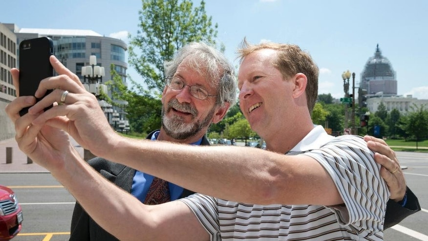 "Patrick Benko of Germantown, Md., left, takes a photograph with Douglas Hughes, the gyrocopter pilot who landed on the West Front of the U.S. Capitol, as Hughes leaves Federal Court after a status hearing Monday June 22, 2015, in Washington. Benko recognized Hughes and asked to take a photograph with him with the U.S. Capitol in the background, ""he made a bold statement,"" says Benko, ""that probably not a lot of people have with the government."" Hughes said he's rejected a plea offer in the case that would have involved several years in prison. (AP Photo/Jacquelyn Martin)"