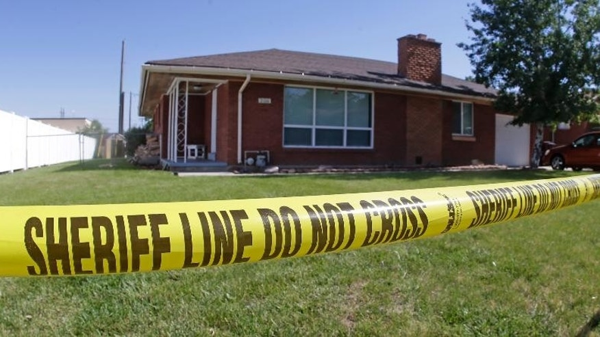 Police tape is hangs in front of the home where a Utah family of four was found shot to death in what authorities believe is a murder-suicide, Monday, June 22, 2015, in Roy, Utah. Officers discovered the bodies of Russell Smith, 29; his wife, Shawna Smith, 26; and their children, 6-year-old daughter Tylee and 2-year-old son Blake on Sunday night. (AP Photo/Rick Bowmer)