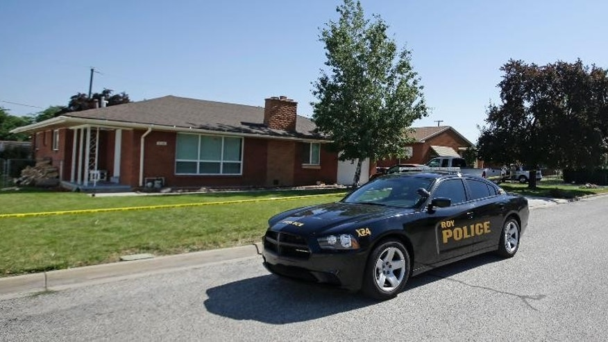 A Roy Police vehicle drives pass the home where a Utah family of four was found shot to death in what authorities believe is a murder-suicide Monday, June 22, 2015, in Roy, Utah. Officers discovered the bodies of Russell Smith, 29; his wife, Shawna Smith, 26; and their children, 6-year-old daughter Tylee and 2-year-old son Blake on Sunday night. (AP Photo/Rick Bowmer)