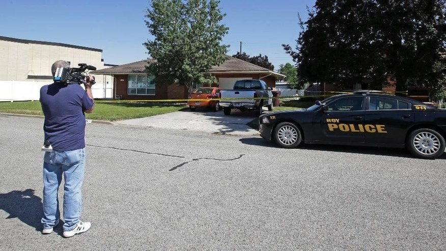 A Roy Police vehicle sits outside the home where a Utah family of four was found shot to death in what authorities believe is a murder-suicide Monday, June 22, 2015, in Roy, Utah. Officers discovered the bodies of Russell Smith, 29; his wife, Shawna Smith, 26; and their children, 6-year-old daughter Tylee and 2-year-old son Blake on Sunday night. (AP Photo/Rick Bowmer)