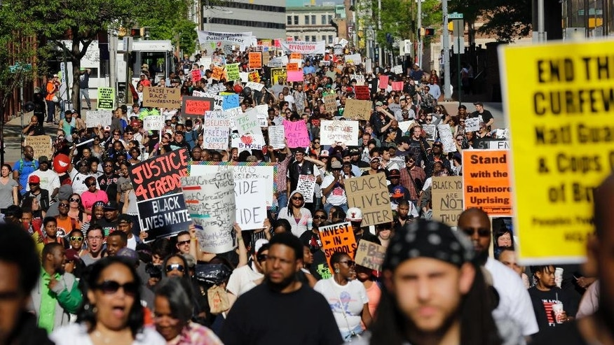 "FILE- In this May 2, 2015 file photo, protesters march through Baltimore the day after charges were announced against the police officers involved in Freddie Gray's death. A medical examiner found Freddie Gray suffered a ""high-energy injury,"" most likely caused when the Baltimore police van he was riding in braked sharply, according to an autopsy report obtained by The Baltimore Sun. (AP Photo/Patrick Semansky, File)"