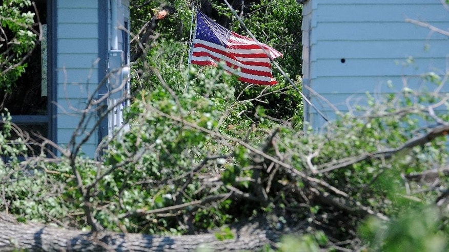 An American flag waves in the wind after severe weather moved through the area, damaging trees, homes and other structures Monday, June 22, 2015, in Garretson, S.D. Thunderstorms caused damage throughout eastern South Dakota, leaving thousands of people without power and zeroing in on the town of Garretson, where damage was particularly extensive. (Joe Ahlquist/The Argus Leader via AP) NO SALES