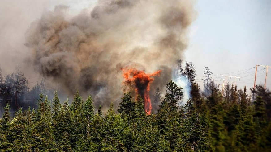 In this June 17, 2015 photo from the Alaska Army National Guard, trees erupt in flames in the Stetson Creek Fire near Cooper Landing, Alaska. Crews have wrangled two large wildfires north and south of Anchorage as dozens of blazes burn over 100 square miles in Alaska. One fire forced the evacuation of campsites on the Kenai Peninsula and destroyed at least eight structures since Monday. (Sgt. Balinda O'Neal/U.S. Army National Guard via AP)