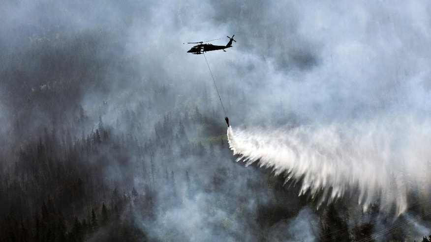 "In this June 17, 2015 photo from the Alaska Army National Guard, a ""Bambi Bucket,"" hanging from a helicopter releases hundreds of gallons of water onto the Stetson Creek Fire near Cooper Landing, Alaska. Crews have wrangled two large wildfires north and south of Anchorage as dozens of blazes burn about 160 square miles in Alaska. One fire forced the evacuation of campsites on the Kenai Peninsula and destroyed at least eight structures since Monday. Altogether, 49 active fires are burning in three western states. (Sgt. Balinda O'Neal/U.S. Army National Guard via AP)"