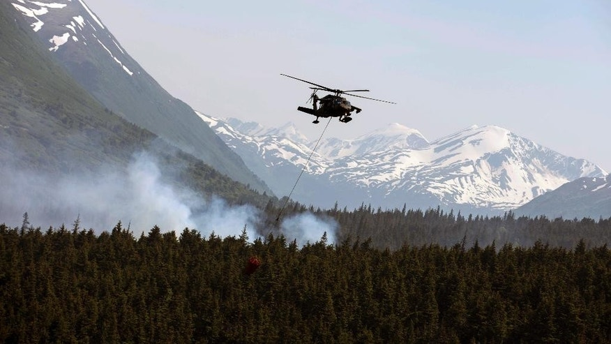 "In this June 17, 2015 photo from the Alaska Army National Guard, a ""Bambi Bucket,"" hanging from an ANG Black Hawk helicopter releases hundreds of gallons of water onto the Stetson Creek Fire near Cooper Landing, Alaska. Crews have wrangled two large wildfires north and south of Anchorage as dozens of blazes burn about 160 square miles in Alaska. One fire forced the evacuation of campsites on the Kenai Peninsula and destroyed at least eight structures since Monday. Altogether, 49 active fires are burning in three western states.(Sgt. Balinda O'Neal/U.S. Army National Guard via AP)"