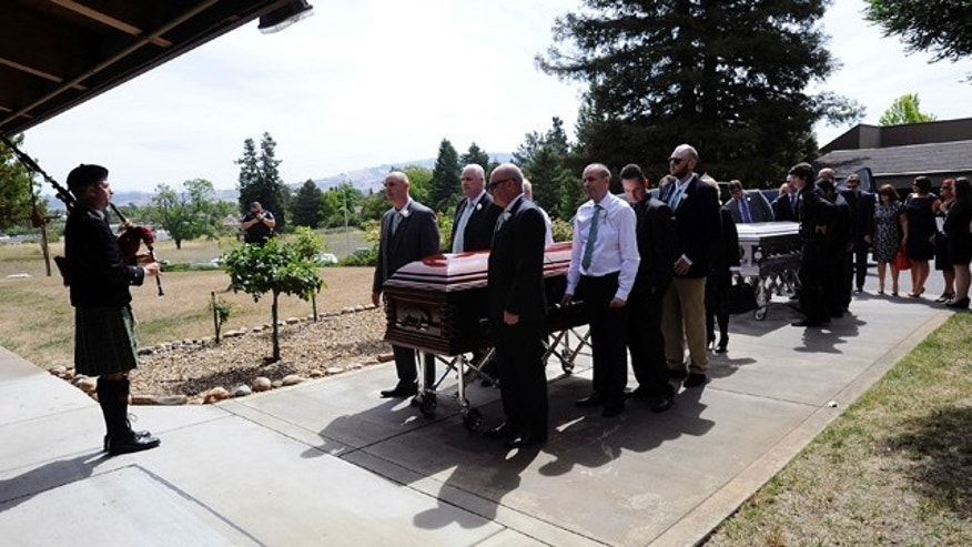 FILE- In this Saturday, June 20, 2015 file photo, pallbearers attend to the caskets of Olivia Burke, 21, and Ashley Donohoe, 22, before a service at  St. Joseph Catholic Church in Cotati, Calif. The two woman were among the several people killed when a balcony snapped off the fifth floor of a Berkeley apartment building during a birthday party. The seven Irish students who survived a balcony collapse remain hospitalized in varying states of recovery nearly a week later. (AP Photo/Michael Short, File)