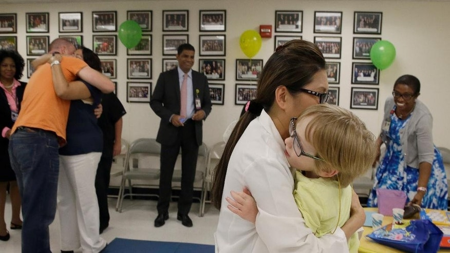 James O'Leary, right, and his father Brett, left, are hugged by members of Bellevue hospital neonatal team that helped care for him at a party in his honor,  Wednesday, June 24, 2015, in New York. James O'Leary was born by surprise, a world away from his home in Australia. His mother was six months pregnant when she went into labor on a vacation in New York. Nearly six years later, he and his father visited Bellevue hospital Wednesday to thank the doctors, nurses and others who cared for him. (AP Photo/Mary Altaffer)
