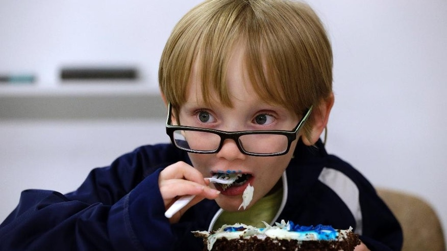 James O'Leary eats cake at a party in his honor given by Bellevue hospital's neonatal team that cared for him Wednesday, June 24, 2015, in New York. James was born by surprise, a world away from his home in Australia. His mother was six months pregnant when she went into labor on a vacation in New York. Nearly six years later, he and his father visited Bellevue hospital Wednesday to thank the doctors, nurses and others who cared for him. (AP Photo/Mary Altaffer)