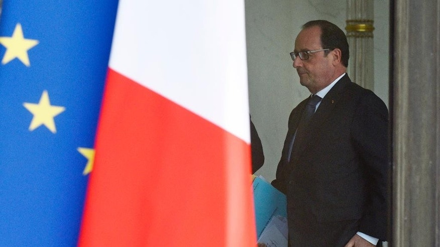 French President Francois Hollande walks through the lobby of the Elysee Palace after the weekly cabinet, Wednesday, June 24, 2015 in Paris, France. France summoned the U.S. ambassador to the Foreign Ministry on Wednesday following revelations by WikiLeaks that the U.S. National Security Agency eavesdropped on the past three French presidents. (AP Photo/Kamil Zihnioglu)