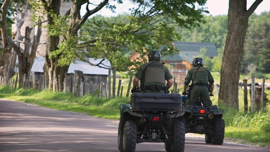 U.S. Border Patrol agents search for two escaped prisoners from Clinton Correctional Facility, Wednesday, June 24, 2015, in Malone, N.Y. Hundreds of searchers checked all-terrain vehicle trails and logging roads and went door-to-door in far northern New York trying to close in on David Sweat and Richard Matt, who escaped from the maximum-security prison more than two weeks ago. (Jason Hunter/The Watertown Daily Times via AP)  SYRACUSE OUT MANDATORY CREDIT