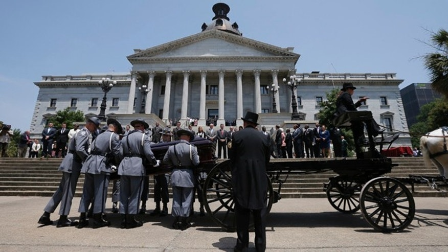 June 24: Pallbearers lower the casket of the late South Carolina State Senator Clementa Pinckney from a caisson in front of the South Carolina State House in Columbia.