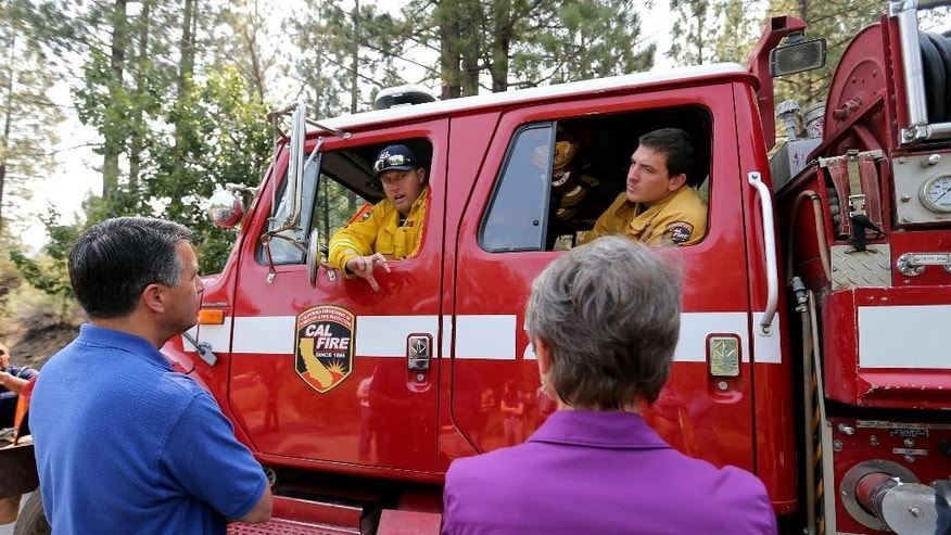 Nevada Gov. Brian Sandoval, left, and U.S. Secretary of the Interior Sally Jewell, right, talk with Cal Fire Capt. Chris Guidice, left, and Firefighter Brandon White in Markleeville, Ca. on Wednesday, June 24, 2015. The lightning-caused Washington fire has grown to nearly 17,000 acres since Friday. (AP Photo/Cathleen Allison)