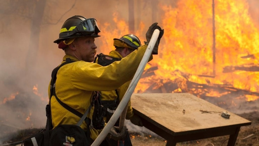 In this May 25, 2014 file photo, Central Emergency Services firefighter Dan Jensen maneuvers a hose into position to fight a portion of a wildfire in the Funny River community of Soldotna, Alaska. Wildfires are blistering Alaska forests with increasing frequency and intensity and forest managers and climate scientists are trying to explain why and predict what's next. One common factor associated with the increase, which doesn't bode well for 2015 or beyond, is warm weather, even if experts don't explicitly blame climate change. (Rashah McChesney/Peninsula Clarion via AP)