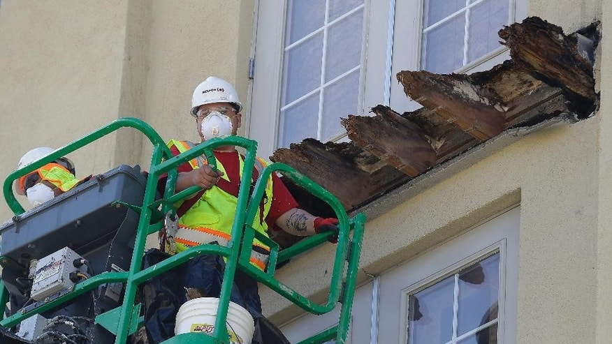 FILE - In this June 18, 2015, file photo, a crew works on the remaining wood of an apartment building balcony that collapsed in Berkeley, Calif. A balcony broke loose from an apartment building during a 21st birthday party early Tuesday, June 16, 2015, killing several and seriously injuring several others. Prosecutors in the San Francisco Bay Area say they will lead a criminal investigation into the Berkeley balcony collapse that killed six college students. The development comes after building inspectors said the fifth-floor balcony that snapped off an apartment building was supported by wooden beams badly rotted by exposure to moisture. (AP Photo/Jeff Chiu, File)