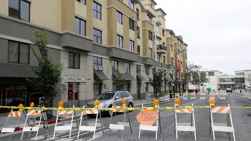 FILE - In this Wednesday, June 17, 2015, file photo, Police tape blocks off a section of Kittredge Street in front the Library Gardens apartment building where balcony collapsed in Berkeley, Calif.  Prosecutors in the San Francisco Bay Area say they will lead a criminal investigation into the Berkeley balcony collapse that killed six college students. The development comes after building inspectors said the fifth-floor balcony that snapped off an apartment building was supported by wooden beams badly rotted by exposure to moisture. (AP Photo/Jeff Chiu, File)