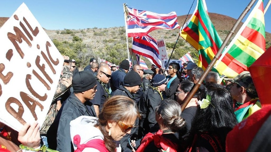 Hilo police face off with protestors Wednesday, June 24, 2015, at the Maunakea Visitors Center in Hilo, Hawaii. Construction on the Thirty Meter Telescope is set to resume Wednesday after a nearly two-month delay in construction. Protesters oppose the project because it will be built on land held sacred by many Native Hawaiians. (Jamm Aquino/The Star-Advertiser via AP) MANDATORY CREDIT, NO SALES