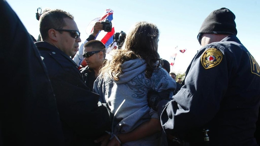 A protector is led away by Hilo Police after being arrested on Wednesday, June 24, 2015, at the Maunakea Visitors Center in Hilo, Hawaii. Construction on the Thirty Meter Telescope is set to resume Wednesday after a nearly two-month delay in construction. Protesters oppose the project because it will be built on land held sacred by many Native Hawaiians. (Jamm Aquino/The Star-Advertiser via AP) MANDATORY CREDIT, NO SALES