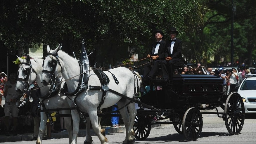 Sen. Clementa Pinckney's remains arrive by horse drawn carriage at the South Carolina Statehouse, Wednesday, June 24, 2015, in Columbia, S.C. Pinckney's open coffin was being put on display under the dome where he served the state for nearly 20 years. Pinckney was one of those killed in a mass shooting at the Emanuel AME Church in Charleston. (AP Photo/Rainier Ehrhardt)