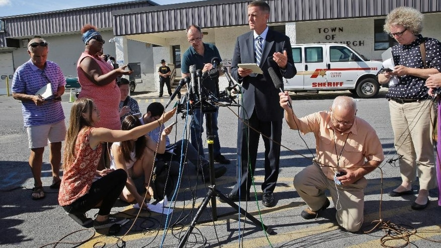Clinton County District Attorney Andrew Wylie, third from right, speaks to reporters, Thursday, June 25, 2015, in Plattsburgh, N.Y. Gene Palmer was set to be arraigned Thursday on charges of promoting prison contraband, tampering with physical evidence and official misconduct. But the court date was rescheduled for Monday. (AP Photo/Mary Altaffer)