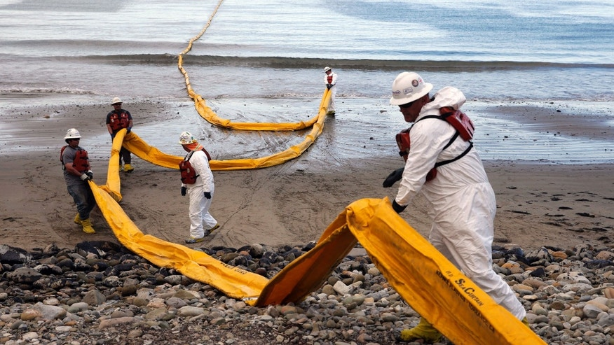 May 21, 2015: Workers prepare an oil containment boom at Refugio State Beach, north of Goleta, Calif.