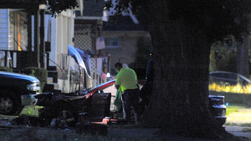 Detroit Police officers check out the damage to a car involved in a police chase on Wednesday, June 24, 2015 in Detroit.  A driver accelerated to more than 70 mph on a residential street in Detroit while fleeing officers before striking and killing two young children and injuring three other children and an adult, police said. (Steve Perez/Detroit News via AP)  DETROIT FREE PRESS OUT; HUFFINGTON POST OUT