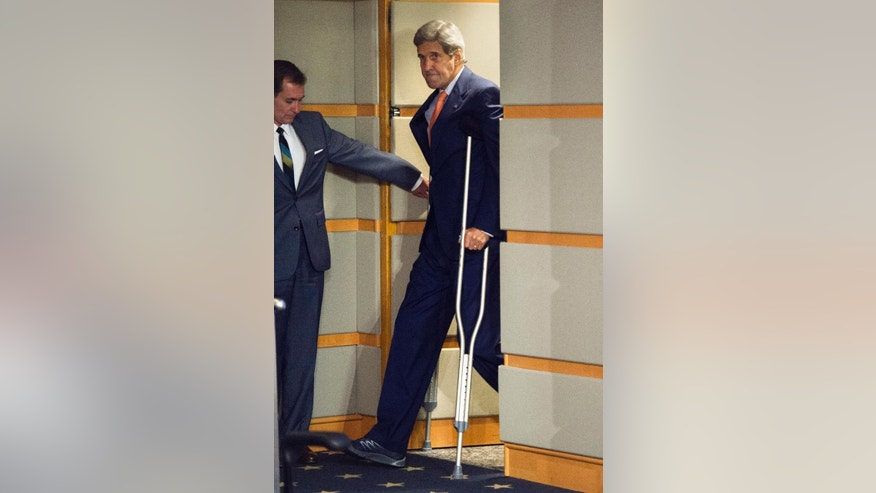 A door is held open as Secretary of State John Kerry arrives in the press briefing room with crutches to speak after the State Department released it's annual human rights reports, Thursday, June 25, 2015, at the State Department in Washington. The Obama administration has once again identified Iran and Cuba as serial human rights abusers even as it accelerates attempts to improve relations with both countries. (AP Photo/Cliff Owen)