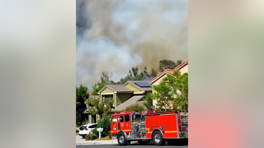 A Los Angeles County fire truck sits stationed in front of homes as smoke billows up in the background, Wednesday, June 24, 2015, in Santa Clarita, Calif. The Los Angeles County Sheriff's Department says 1,000 people have been evacuated from homes as a 100-acre wildfire burns through brushy canyonlands north of Los Angeles. (AP Photo/Rick McClure)