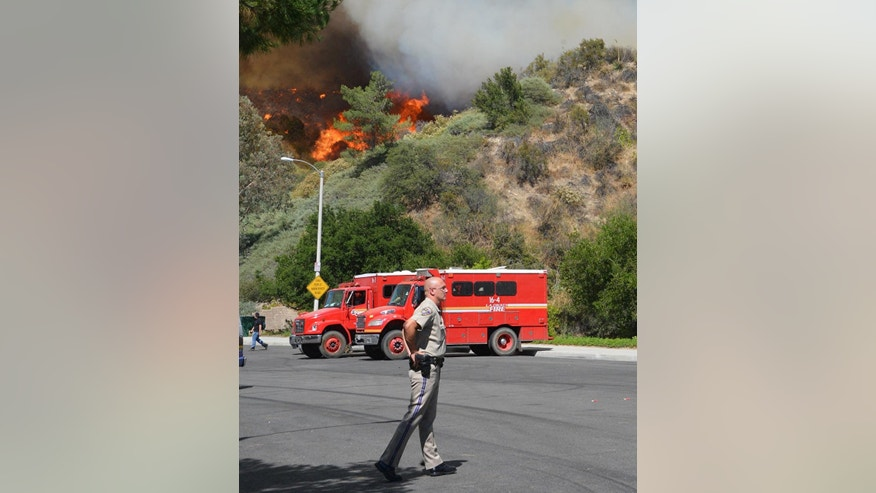 A California Highway Patrol officer stands by as a hillside burns in the background, Wednesday, June 24, 2015, in Santa Clarita, Calif. The Los Angeles County Sheriff's Department says 1,000 people have been evacuated from homes as a 100-acre wildfire burns through brushy canyonlands north of Los Angeles. (AP Photo/Rick McClure)