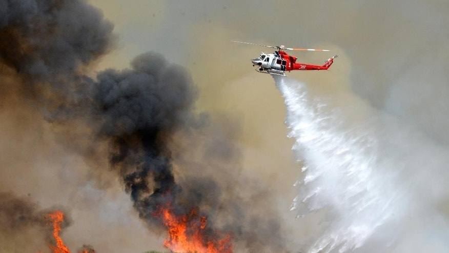 A Los Angeles City Fire helicopter drops water on flames, Wednesday, June 24, 2015, in Santa Clarita, Calif. About 1,000 people have been evacuated from homes as a 100-acre wildfire burns through brushy canyonlands north of Los Angeles. (AP Photo/Rick McClure)