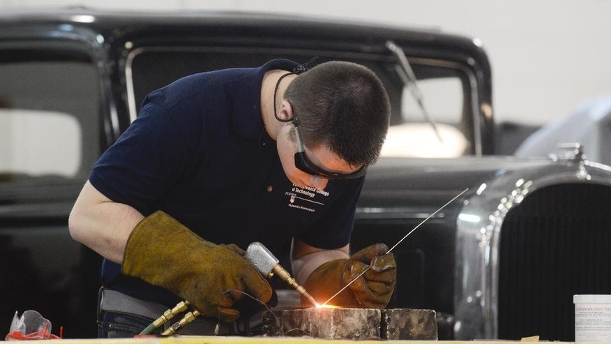 In this March 26, 2015, photo, Sean Hunter tests gas welds on aluminum while working on a 1935 Rolls Royce at Pennsylvania College of Technology in Williamsport, Pa. When Penn College of Technology revved up its vintage vehicle restoration major in 2012, it became one of just a handful of degree programs around the country teaching teens and 20-somethings how to help refurbish and maintain North America's fleet of more than 10 million classic cars. (AP Photo/Ralph Wilson)