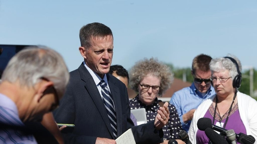 Clinton County District Attorney Andrew Wylie, third from right, speaks to reporters, Thursday, June 25, 2015, in Plattsburgh, N.Y. Gene Palmer, the U.S. prison guard charged in connection with the escape of two killers, admitted providing them with tools, paint, frozen hamburger meat and access to a catwalk electrical box, but claims he never knew they planned to bust out, authorities say. (AP Photo/Mary Altaffer)