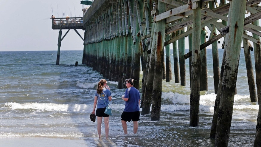 June 15, 2015: Doug Baucom, right, of Wadesboro, talks with his daughter Katie Reynolds, left, of Boone, N.C., as they stand in the surf by the Ocean Crest Pier in Oak Island, N.C.,